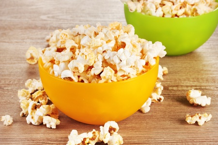 popcorn bowls: popcorn in bright plastic bowls on wooden table