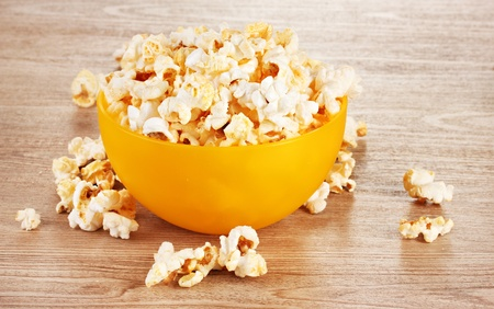 popcorn in bright plastic bowl on wooden table photo