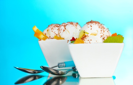 plastic scoop: delicious vanilla ice cream with chocolate and fruits in bowls and spoons on blue background