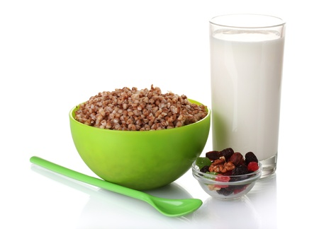 Boiled buckwheat in a green bowl a glass of milk isolated on white photo