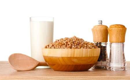 Boiled buckwheat in a wooden bowl with a glass of milk on wooden table isolated on white photo