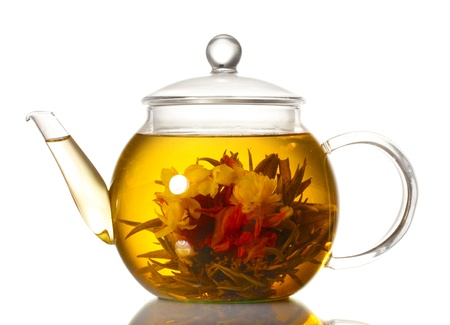 exotic green tea with flowers in glass teapot isolated on white photo