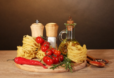 mediterranean home: noodles in bowl, jar of oil, spices and vegetables on wooden table on brown background