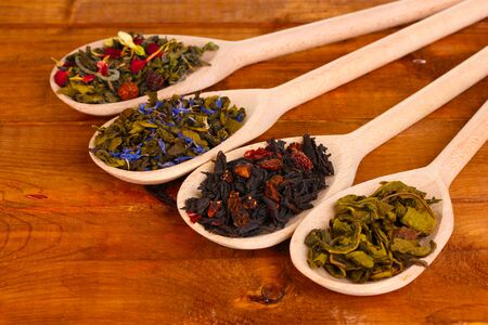 Different kinds of dry green and black tea in spoons on wooden background photo
