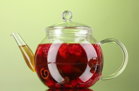 Glass teapot with fruit raspberry tea on green background photo