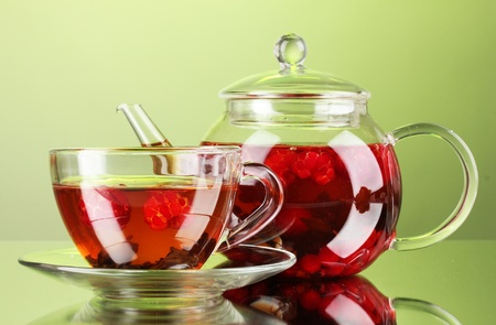 Black fruit raspberry tea in glass teapot and cup on green background Stock Photo - 11517501