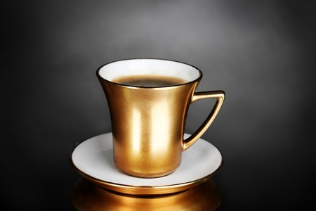 porcelain: golden cup of coffee on gray background Stock Photo