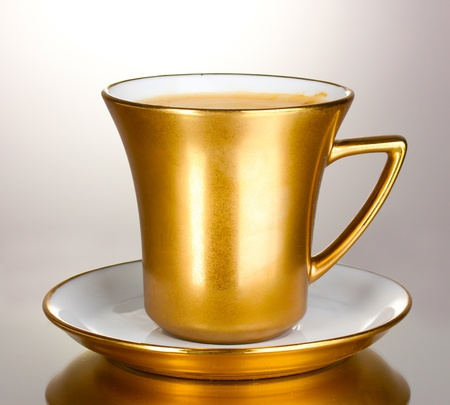 golden cup of coffee isolated on white photo