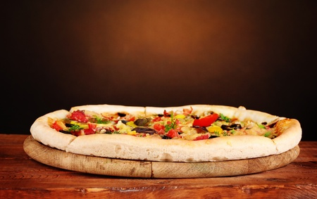 delicious pizza with vegetables on wooden table on brown background photo