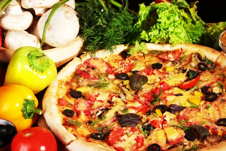 delicious pizza, vegetables and spices on wooden table photo