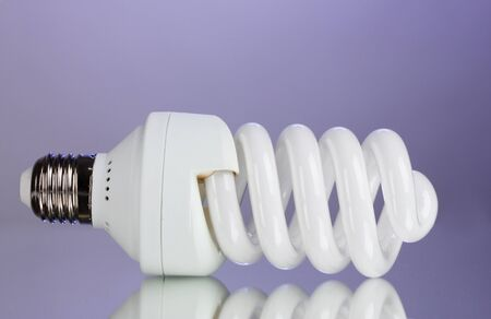 energy saving light bulb on purple background  photo