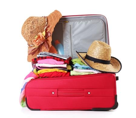 maleta: Abra la maleta roja con la ropa aislada en un blanco Foto de archivo