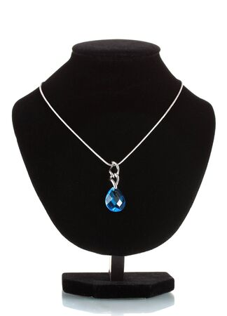 Pendant with blue gem on mannequin isolated on white photo