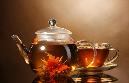 glass teapot and cup with exotic green tea on wooden table on brown background Stock Photo - 11665265