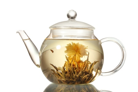 chinese teapot: exotic green tea with flowers in glass teapot isolated on white Stock Photo