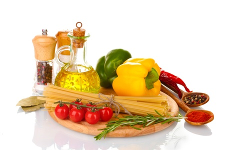 spaghetti, jar of oil, spices and vegetables on wooden board isolated on white photo