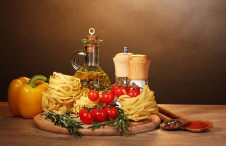 noodles in bowl, jar of oil, spices and vegetables on wooden table on brown background photo