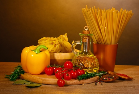 spaghetti, noodles in bowl, jar of oil and vegetables on wooden table on brown background photo