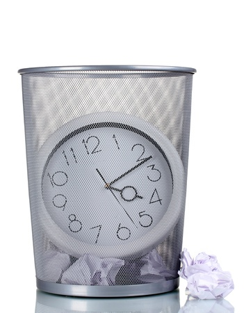 Wall Clock in metal trash bin and paper isolated on white photo
