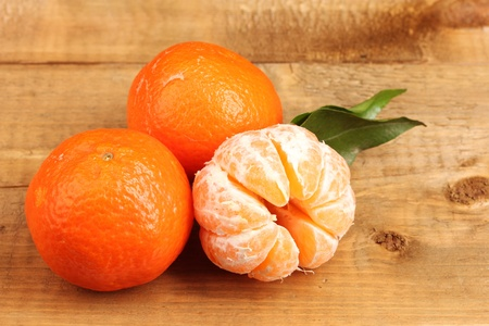 tangerines with leaves on wooden table photo