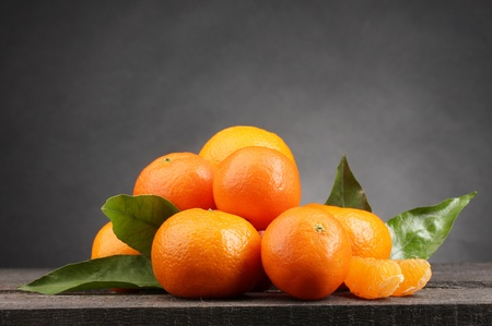 tangerine: tangerines with leaves on wooden table on grey background