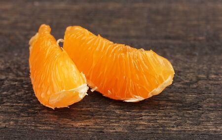 orange peel clove: due spicchi di mandarino maturo sul tavolo di legno grigio Archivio Fotografico