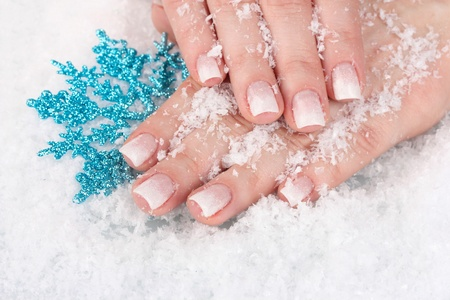 hands with snow and snowflake closeup photo