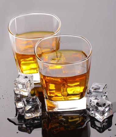 scotch: twee glazen whisky whiskey en ijs op de grijze lijst Stockfoto