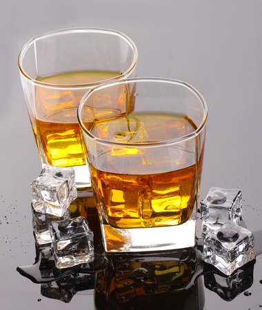 hard liquor: two glasses of scotch whiskey and ice on grey table Stock Photo