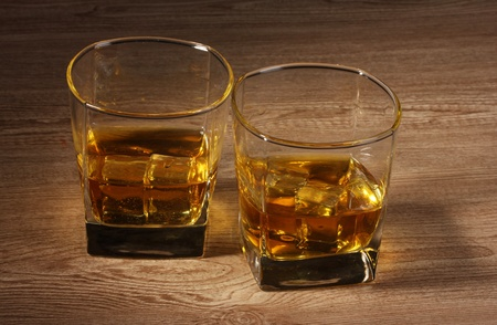 whisky: two glasses of scotch whiskey and ice on wooden table Stock Photo