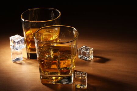 two glasses of scotch whiskey and ice on wooden table photo