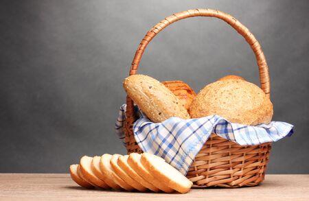 canasta de panes: delicioso pan en la canasta en la mesa de madera sobre fondo gris