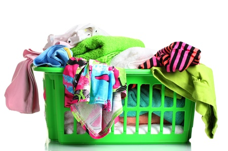 Clothes in green plastic basket isolated on white photo