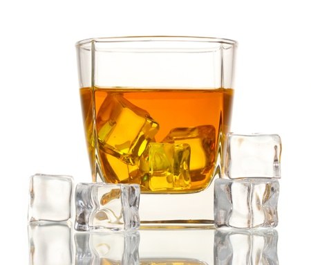 Glass of scotch whiskey and ice isolated on white photo