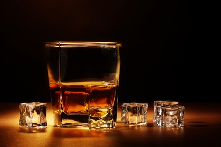 glass of scotch whiskey and ice on wooden table on brown background photo