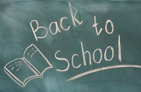 Back to school written on green chalkboard photo