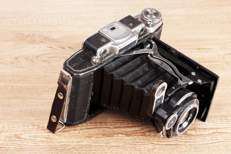 Old photo camera on wooden background photo