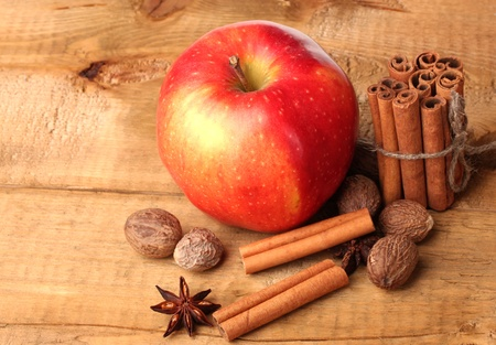 Cinnamon sticks,red apple, nutmeg,and anise on wooden table photo