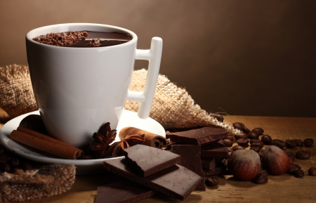 hot cocoa: cup of hot chocolate, cinnamon sticks, nuts and chocolate on wooden table on brown background