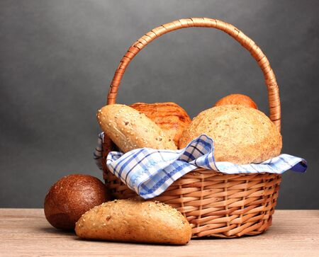 delicious bread in basket on wooden table on gray background photo