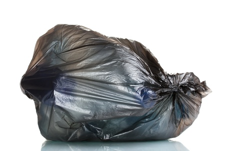black garbage bag with trash isolated on white photo