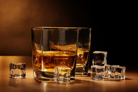 two glasses of scotch whiskey and ice on wooden table on brown background