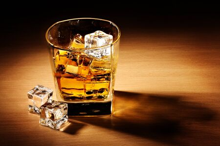 glass of scotch whiskey and ice on wooden table photo