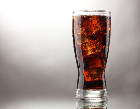 tall glass: Glass of cola with ice on grey background Stock Photo