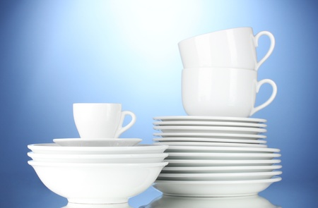 clean dishes: empty bowls, plates and cups on blue background