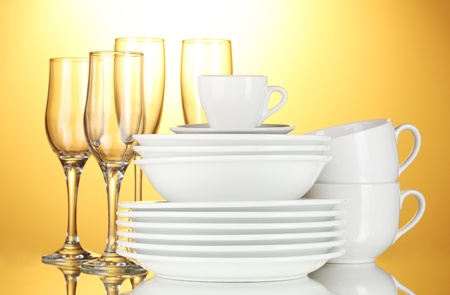 cater: empty bowls, plates, cups and glasses on yellow background Stock Photo