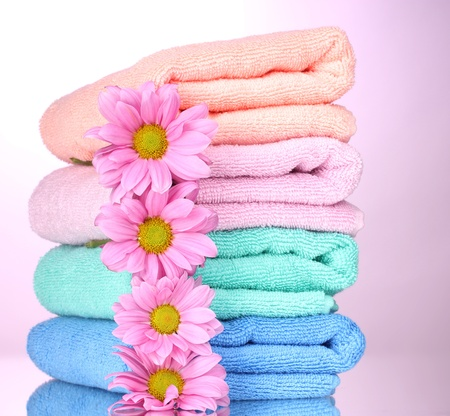 towels and beautiful flowers on pink background photo