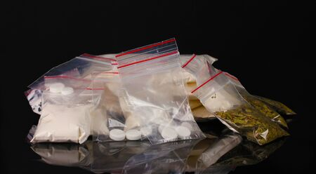 Cocaine and marihuana in packages on black background Stock Photo - 11831803