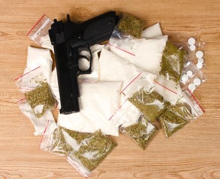 illicit: La cocaina e marijuana in pacchetti e pistola su fondo in legno