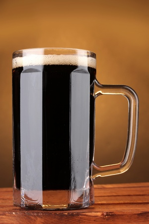 dark beer in a mug on wooden table on brown background Stock Photo - 11831951